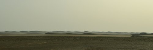 Big flowing dunes beyond the stony desert.